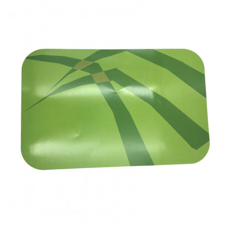 Grönt bordsunderlägg med inslag av mörkgröna partier. Av papper.