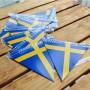 Girlang med sverigeflaggor som ligger mot ett bord.