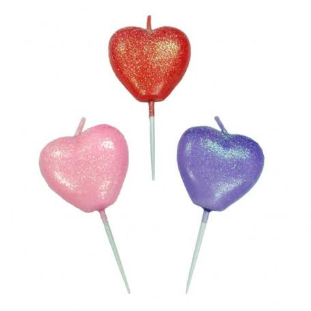 Tårtljus formade som hjärtan i rosa, lila och rött.